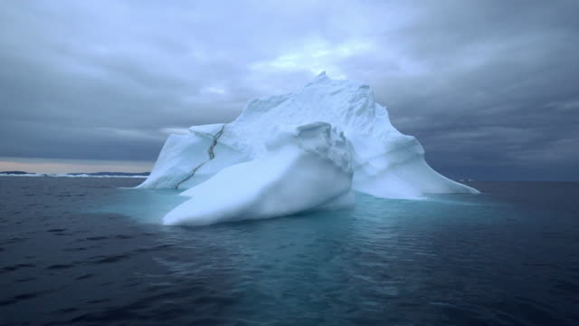 pan: magnificent iceberg in dark waves on disko bay after sunset - ice stock videos & royalty-free footage