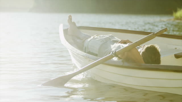 ms pan tu of man asleep in rowing boat on lake - 小型船舶点の映像素材/bロール