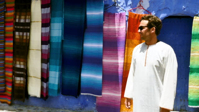 pan: man standing in front of rugs - north africa stock videos & royalty-free footage