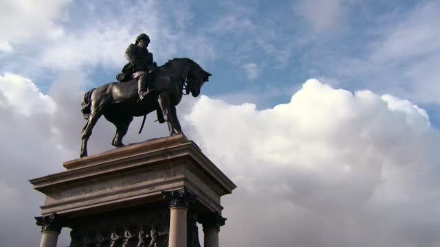 pan: massive bronze statue of earl roberts on a horse before sweeping blue sky with majestic clouds - glasgow, scotland - statue stock videos & royalty-free footage