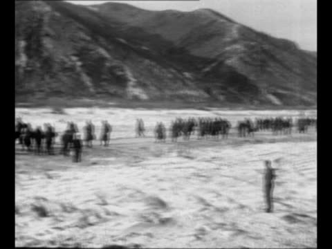pan military encampment in snow during korean war / montage un soldiers walk on snowy road with mountains in background / mortar crew with gun in... - tinsel stock videos & royalty-free footage