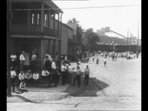 vidéos et rushes de pan mine village during economic slowdown / ws miners mill around in streets children play in far background / miner families sit on steps of their... - pennsylvanie