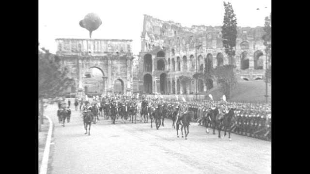 pan mounted italian troops in rome with arch of constantine and coliseum / tracking victor emmanuel iii on horse saluting as he passes troops /... - arch of constantine stock videos and b-roll footage