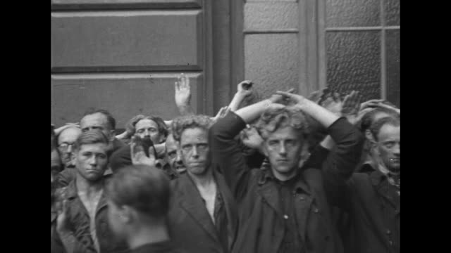 MS pan Nazi prisoners German military and civilian with probably collaborators with hands up or behind heads crowded against EXT building / CU...