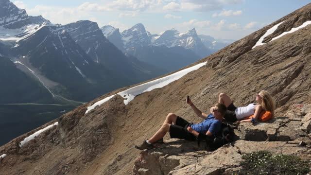 Pan of 2 teens relaxing on top of rocky mtn ridge