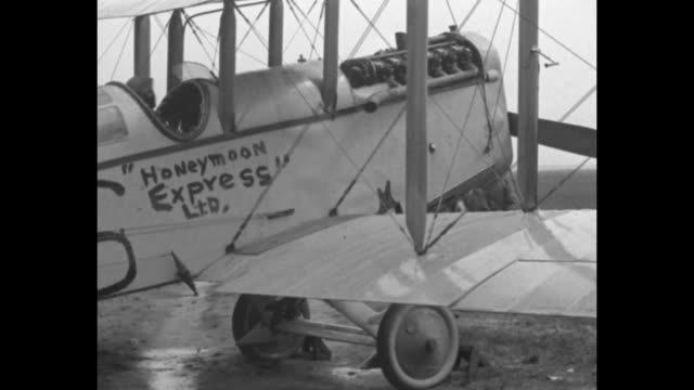 pan of a long line of parked biplanes handpainted sign on side of craft honeymoon express ltd 6 and the ground crew at the propeller / a women kisses... - aerospace stock videos & royalty-free footage