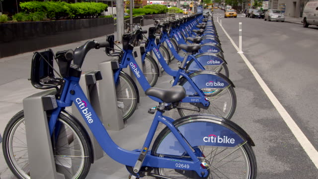 pan of a row of the new citi bikes sit in their corrals waiting to be used.  they are a part of the new bike share program in new york city - group of objects stock videos & royalty-free footage
