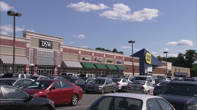 pan of all stores in a shopping center/strip mall stores include new york company bob's discount furniture burlington coat factory dsw and best buy... - centro commerciale suburbano video stock e b–roll