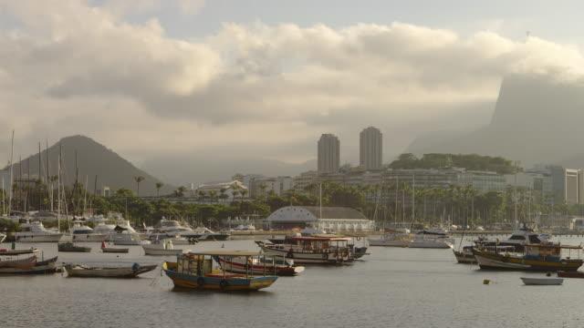 vídeos de stock e filmes b-roll de pan of anchored boats in a hazy rio marina. - 2013