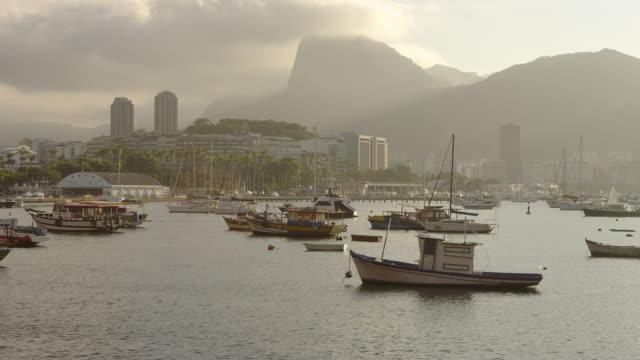 pan of anchored boats in a hazy rio marina. - anchored stock videos & royalty-free footage