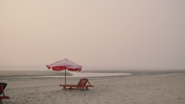 pan of beach chairs and boats in the distance - cox's bazaar stock videos and b-roll footage