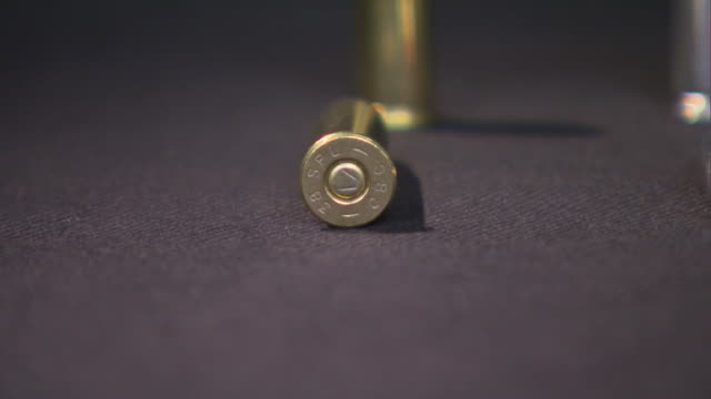 pan of bullets laying down on a tabletop background. - still life stock videos & royalty-free footage