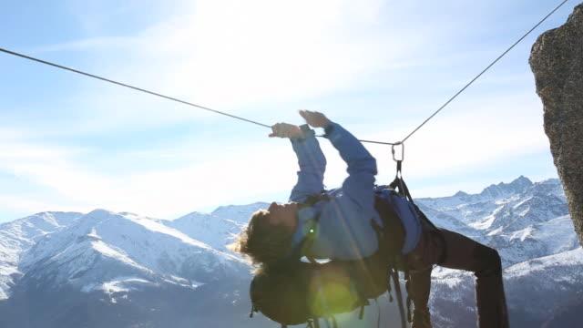 vídeos y material grabado en eventos de stock de pan of climber pulling himself along tyrolean traverse - artículo de montañismo