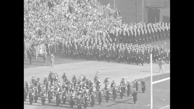 pan of crowded municipal stadium during annual rivalry game between army black knights and navy midshipmen / qs naval midshipmen wave hats in stands... - 士官候補生点の映像素材/bロール