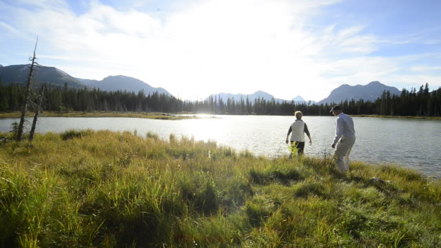 Pan of elderly couple taking a picture of mountain lake