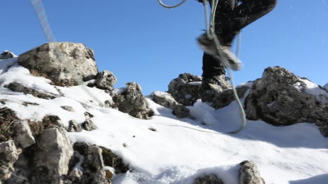 pan of father & son traversing snowy ridge, son slips… - 高み点の映像素材/bロール
