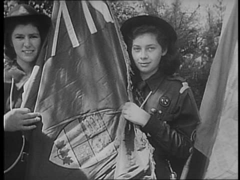Pan of Girl Scouts with flags standing in a row / Eleanor Roosevelt visits Girl Scout camp walks through woods / many rows of Girl Scouts standing in...