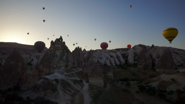 pan of hot air balloons hovering over unusual rock formations - cappadocia, turkey - basalt stock videos & royalty-free footage