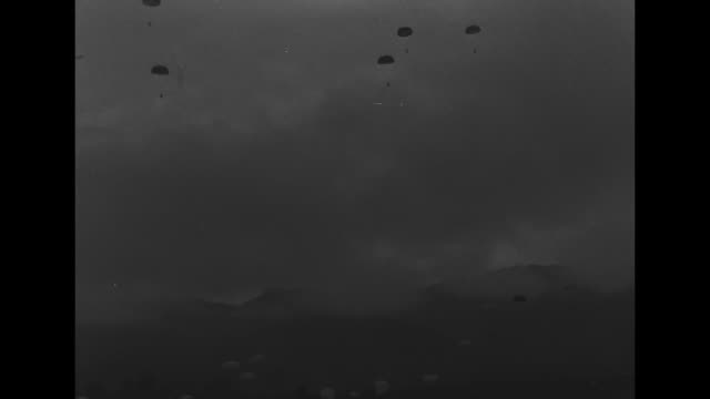 ws pan of indochina war battlefield landscape / pan of parachutists dropping from sky / planes flying / quick shot soldier on the ground in... - französische armee stock-videos und b-roll-filmmaterial