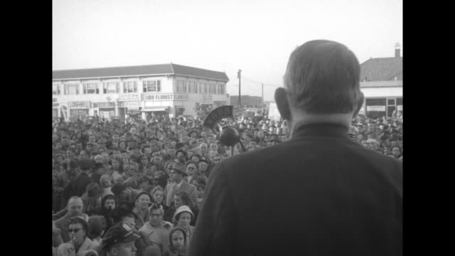 pan of large crowd some adlai stevenson placards seen / vs view of crowd seen over shoulder of vp allen barkley speaking at microphone left profile... - adlai stevenson ii stock videos and b-roll footage