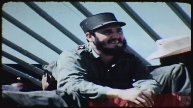 Pan of main stage Fidel Castro looks out speaks with others while waiting for events to begin