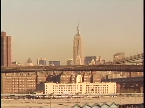 pan of manhattan from brooklyn in the 1980s, zooming in to the brooklyn bridge and empire state building. - 1980 1989 stock videos & royalty-free footage