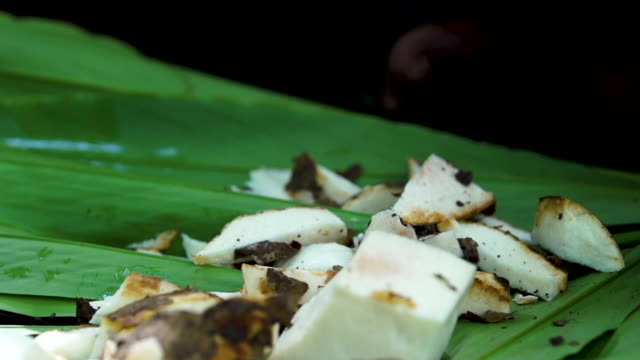 Pan of man's hands cutting coconut slices on bamboo leaves