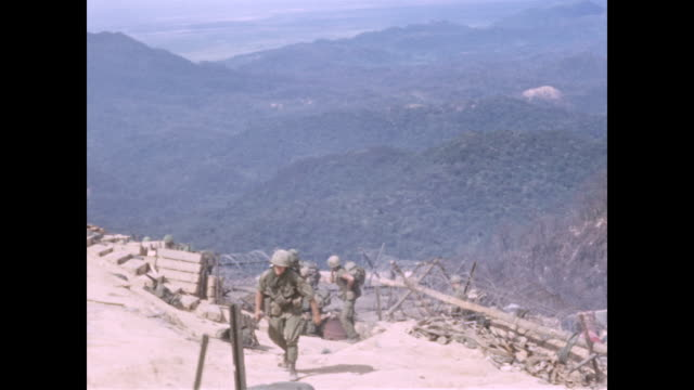 pan of mountains where north vietnamese troops were massing around the besieged artillery base ends with soldiers arriving at fire support base... - north stock videos & royalty-free footage