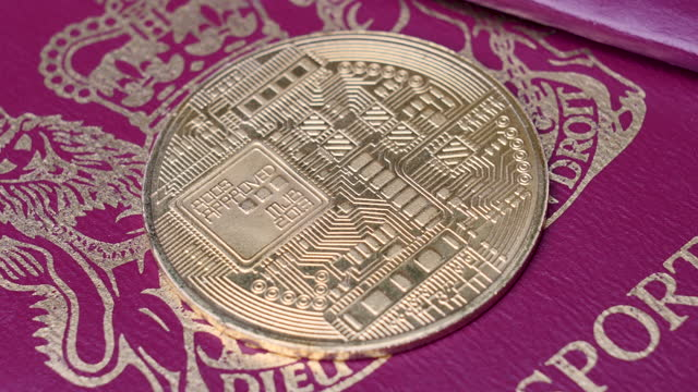 4k pan of new uk digital cbdc cryptocurrency coin with wallet passport background. crypto currency entering mass adoption of hedge funds, family offices, pension funds, venture capital, financial institutions and banks - blockchain stock videos & royalty-free footage