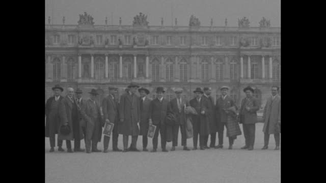 vídeos de stock, filmes e b-roll de pan of numerous men standing in a line in front of the garden facade of the palace of versailles / the latona fountain with a long vista beyond /... - jardim de versailles