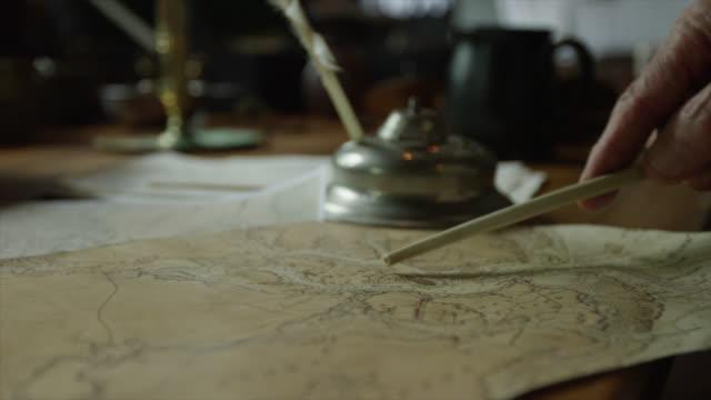 vidéos et rushes de pan de la vieille carte sur une table et un pointeur ponté à des lieux d'intérêt. - image du xviiième siècle