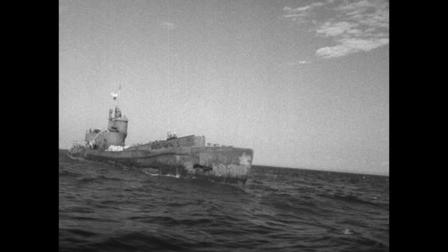 pan of one of japan's largest submaries at sea / submarine at sea / closer view of submarine with sailors and officers aboard and american flag... - pacific war点の映像素材/bロール