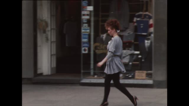 pan of red-haired woman walking down street in 1980s fashion - 1982 stock videos & royalty-free footage