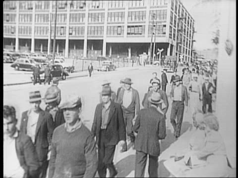 pan of returning workers walking next to onlookers / crowd of workers marching down sidewalk / workers walking through plant entrance - skeppsbyggare bildbanksvideor och videomaterial från bakom kulisserna