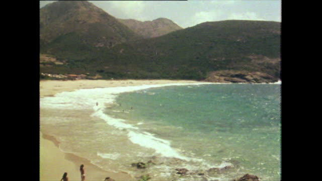 pan of sandy beach and shoreline in devon; 1981 - water's edge stock videos & royalty-free footage