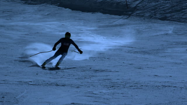 Pan of skier skiing down slope by night.
