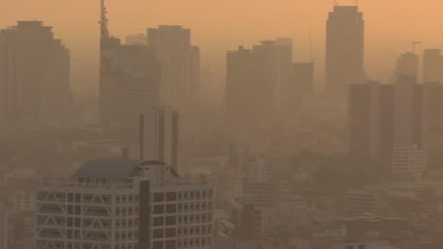 Pan of smoggy Bangkok city skyline at sunset