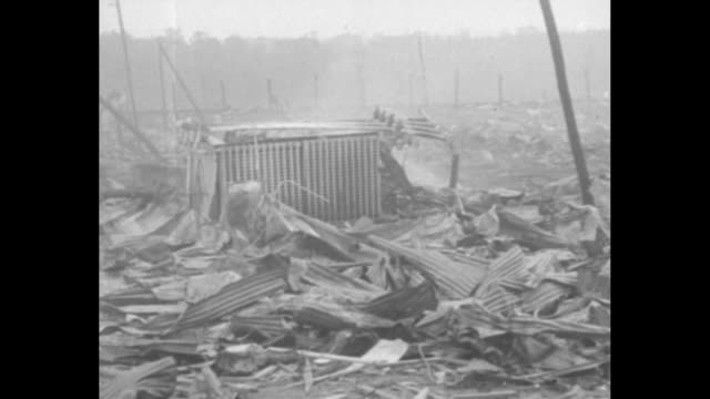 pan of smoldering wreckage site in the distance and shattered material at the side of railroad tracks and an elevated view of men searching through... - paramount building stock videos and b-roll footage
