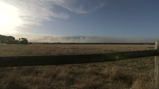 pan of sun and landscape from behind a fence on kangaroo island in australia. smoke is seen in the distance from fires on the island. - environment or natural disaster or climate change or earthquake or hurricane or extreme weather or oil spill or volcano or tornado or flooding stock videos & royalty-free footage