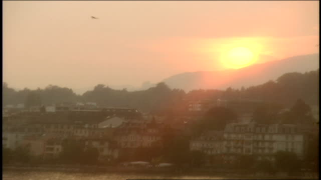 pan of sunset over lake homes and mountain in montreux, switzerland - montreux stock videos & royalty-free footage