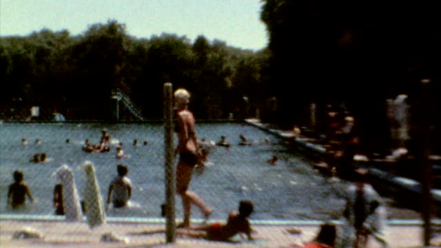 pan of swimming pool and life guard / children playing and diving in the pool / big pool aquatics on july 01 1976 in garden city kansas - kansas city kansas stock videos & royalty-free footage