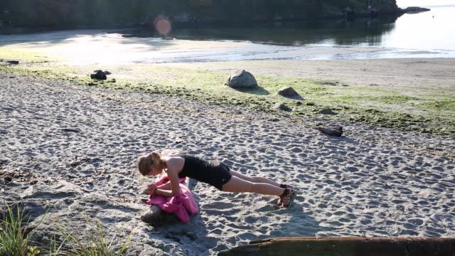 Pan of teenage girl excercising on beach at sunrise