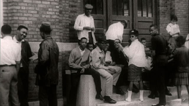 pan of teenagers outside segregated school in chicago; 1964 - アメリカ黒人の歴史点の映像素材/bロール