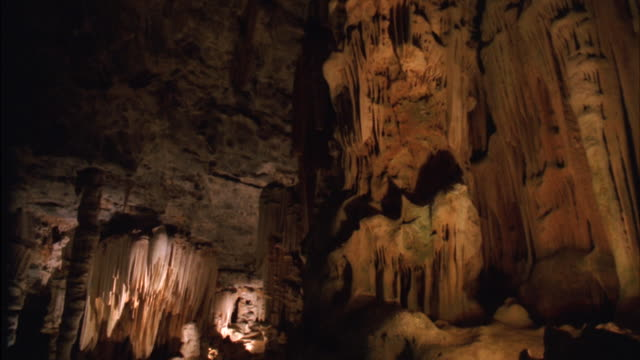 pan of the interior and limestone formations of a cave, with two people carrying flashlights exploring the caves - 石灰岩点の映像素材/bロール