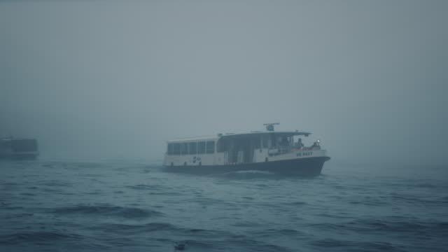 ws - pan of vaporetto leaving giudecca island in the mist - nebbia video stock e b–roll