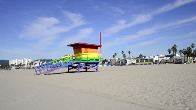 Pan of Venice Beach with a lifeguard tower painted with the rainbow flag colors.