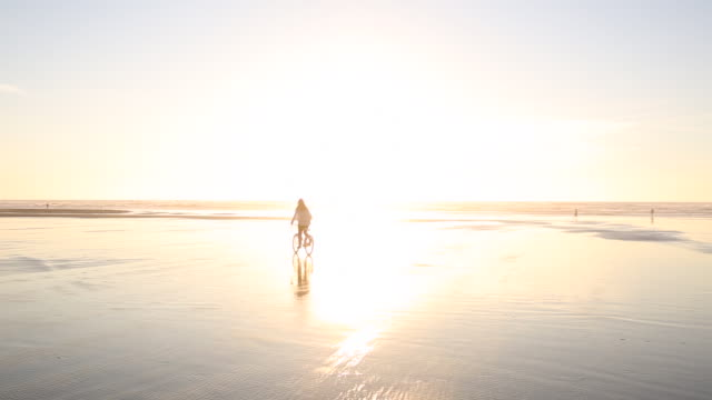 pan of woman biking on wet sand by surf at sunset - oregonkusten bildbanksvideor och videomaterial från bakom kulisserna
