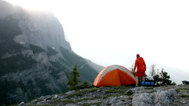 pan of woman standing beside tent - tent stock videos & royalty-free footage