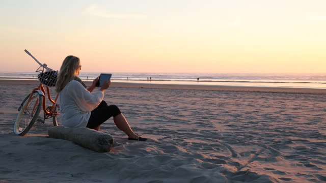 pan of woman taking photo with digital tablet of sun set over ocean with bicycle - costa dell'oregon video stock e b–roll