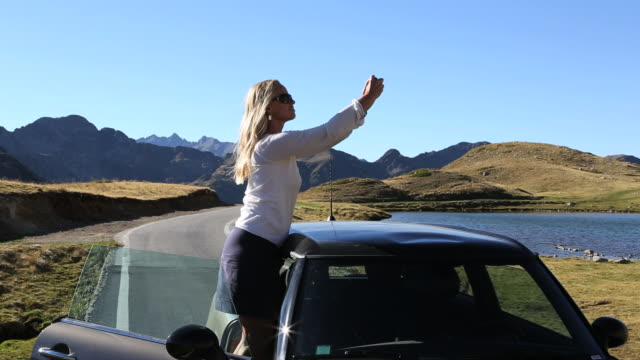 pan of woman taking picture/video with phone, mtn road - one mid adult woman only stock videos & royalty-free footage